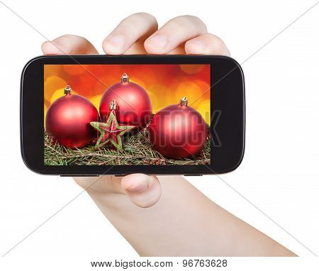 Hand Holds Handphone With Xmas Decorations