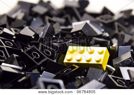 Pile of black color building blocks with selective focus and highlight on one yellow block