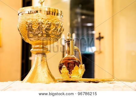 Catholics bread and wine in chalice with crucifix in background