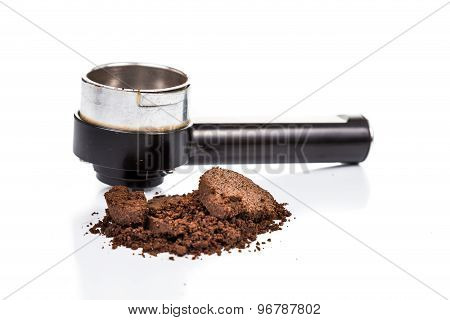 Spent or used coffee grounds with portafilter in the background