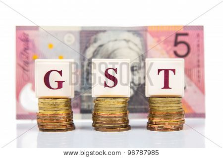 GST or Goods and Services Tax concept with stack of coins and Australian dollar currency as backdrop