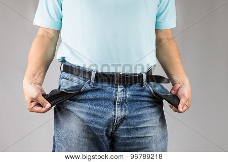 Man in jeans pulling out his empty pockets