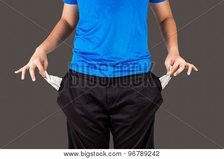 Teenager pulling out his empty pockets from his pants