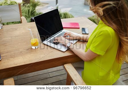 Creative female freelancer sitting front laptop computer with blank copy space screen for your text