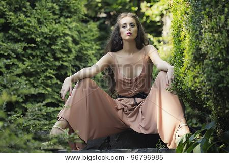 Sexy Woman Sitting In Garden