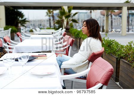 Young charming afro american woman sitting at the table of beautiful open air restaurant