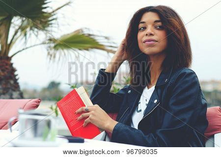 Portrait of charming afro american woman sitting at the coffee shop terrace with book or novel