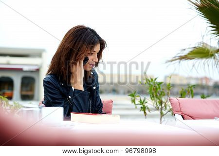 Young female hipster having cell phone conversation with someone at restaurant
