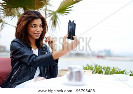 Female tourist using mobile phone camera for take a picture of herself during vacation holidays