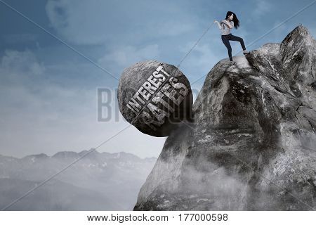 Image beautiful female entrepreneur pulls big rock with text of interest rates while climbing on the mountain
