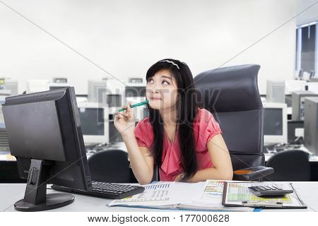 Image of pensive female entrepreneur holding a pen while sitting in the workplace with a computer and paperwork on the desk