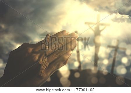 Hands of a Christian man holding a rosary while praying to god with three crucifixes under sunbeam in the hill