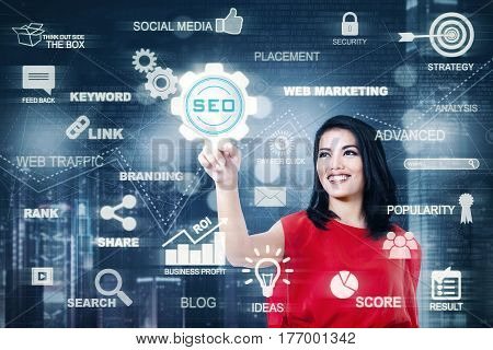 Portrait of happy businesswoman pressing a virtual SEO button on the futuristic screen. SEO concept