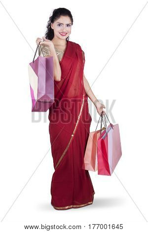 Full length of beautiful Indian woman smiling at the camera while wearing a red saree clothes and holding shopping bags