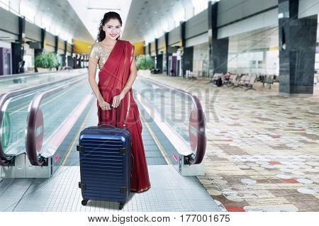 Portrait of a young Indian woman wearing saree clothes and holding a suitcase on the escalator in the airport