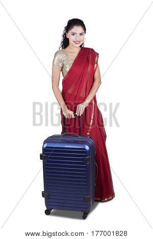 Beautiful Indian woman wearing a red saree and holding a suitcase in the studio isolated on white background