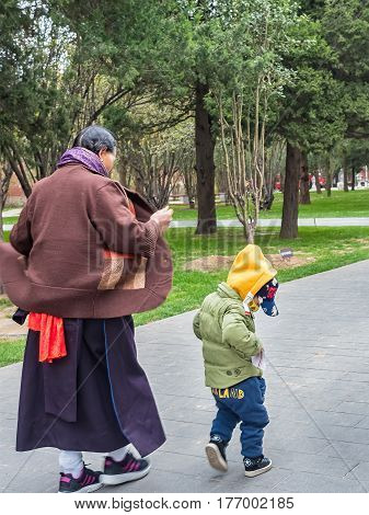 Beijing, China - Oct 30, 2016: Lady in traditional attire walking alongside grandson in the park outside the Forbidden City (Gu Gong, Palace Museum). It was cold and windy.