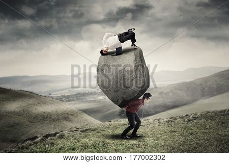 Male worker uses laptop with breakdance pose on the stone while his partner carrying the stone on the hill