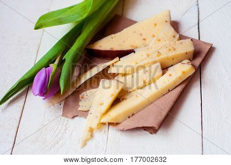 Dutch cheese slices with walnuts and Dutch lilac tulip on a light wooden table.