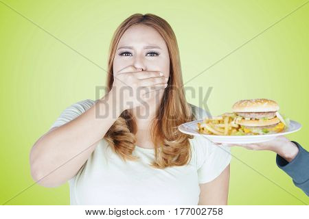 Portrait of obese woman refusing hamburger and french fries on plate while closed her mouth