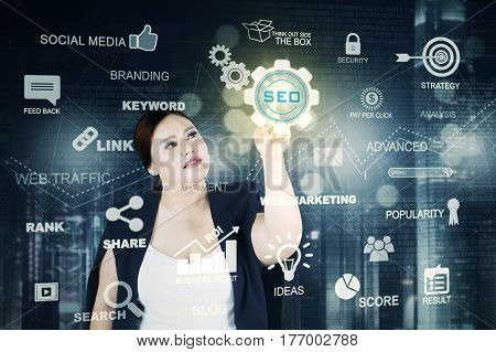 Picture of a pretty overweight businesswoman pressing a virtual SEO button on the digital screen. SEO concept