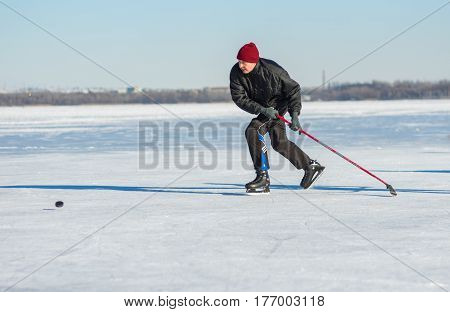 Dnepr Ukraine - January 22, 2017: Mature man desperately trying to catch up the pack while playing hockey on a frozen river Dnepr in Ukraine