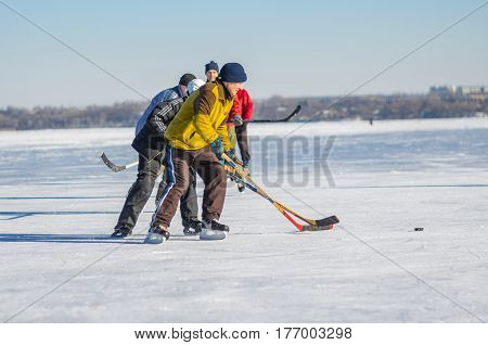 Dnepr Ukraine - January 22 2017: People of different ages playing hockey on a frozen river Dnepr in Ukraine