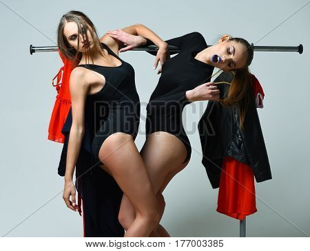 Pretty Girls In Black Sexi Bodysuits Posing At Clothes Rack