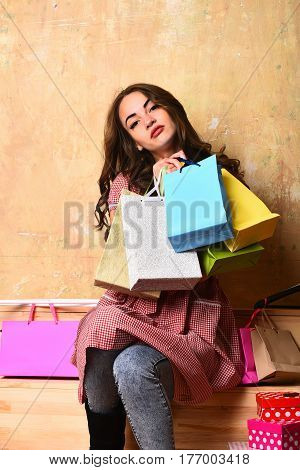 pretty sexy girl or cute fashionable woman with long brunette curly hair holds hangers colorful shopping bags or packages and present boxes on beige background sitting on wooden stairs