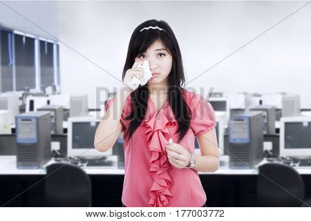 Pretty businesswoman crying in the office room while wiping her tears with a tissue