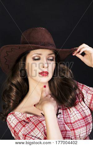 Beautiful brunette cowgirl in cowboy hat on dark background
