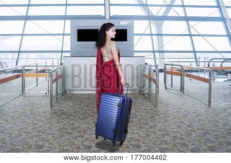 Rear view of Indian woman wearing saree clothes while walking in the airport terminal and carrying a suitcase