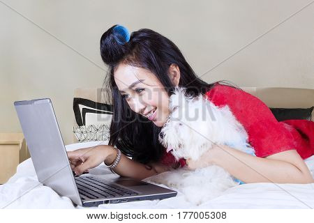 Portrait of beautiful woman pointing at the screen laptop while lying on the bed with Maltese puppy in the bedroom