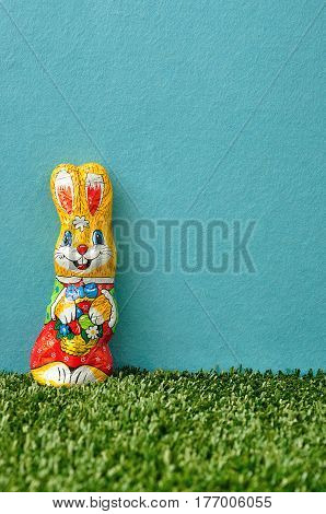 An easter bunny displayed on artificial grass and a blue background