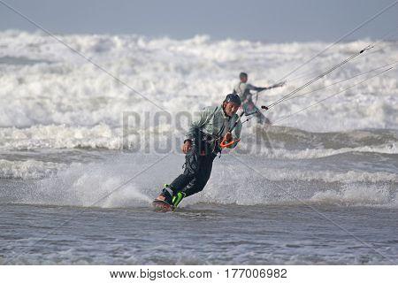 kitesurfer riding his board in breaking waves