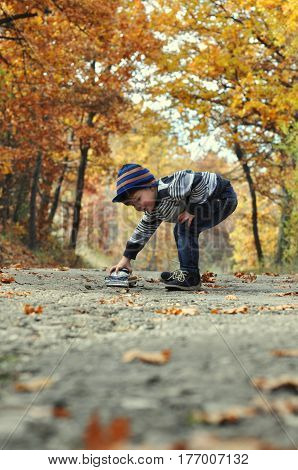 Happy little boy plays with car toy on country road in forest. Kid drive a car toy on the road