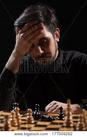 Portrait of adult man who capitulated in chess game. Focus on man.