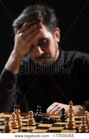 Portrait of adult man who capitulated in chess game. Focus on king figure.