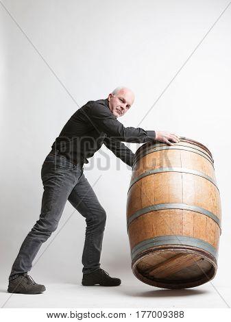 Man Moving A Large Oak Wine Or Beer Barrel