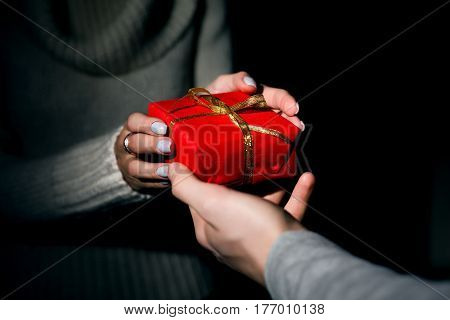 Male and female hands passing decorated red Christas gift box with golden ribbon on black background