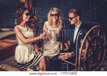 Stylish wealthy friends having fun on a luxury yacht.