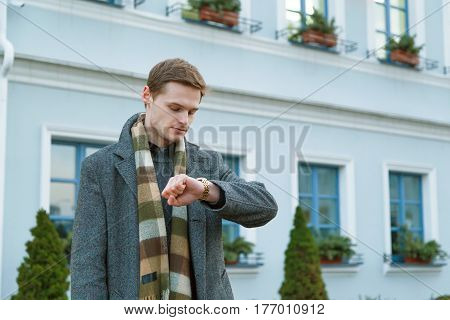 Young man in coat is looking at his watch while standing outdoors in the city. Time appointment Concept