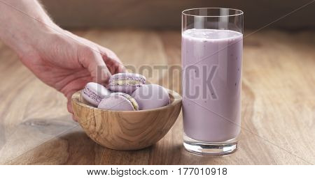 man hand bring violet macarons with blueberry yogurt in glass on wood table, 4k photo