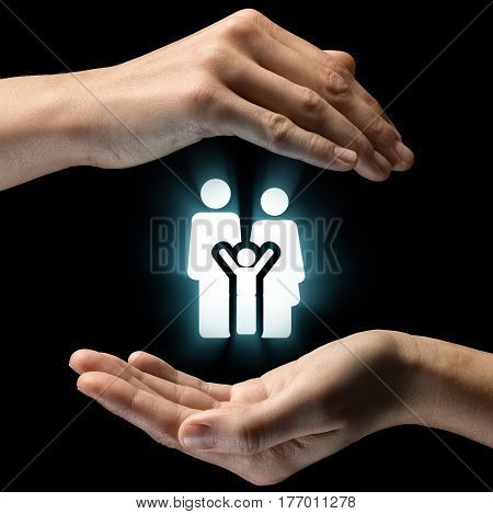 Isolated image of two hands on black background. family icon in the center as a symbol of care for the family. Concept of care for the family and child.