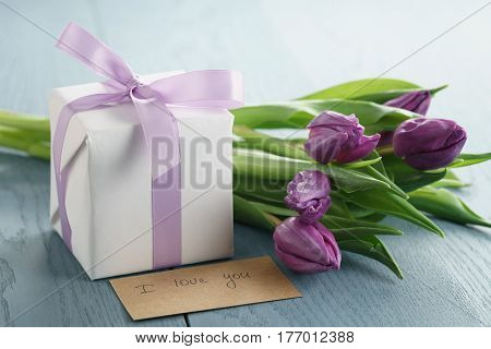 white gift box with purple bow and tulips on blue wood background, i love you paper card