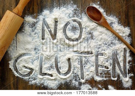 Gluten Free Flour With Text No Gluten In English Language With Wooden Spoon And Rolling Pin On Dark