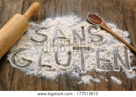 Gluten Free Flour With Text Gluten Free In French Language With Wooden Spoon And Rolling Pin On Dark