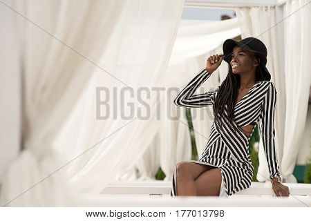 Pretty young dark-skinned girl sitting on a white bench among white fabrics and posing for camera.