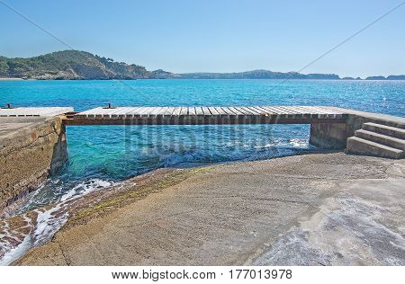 Spring beach sunshine, wooden jetty and ocean in Mallorca Spain.