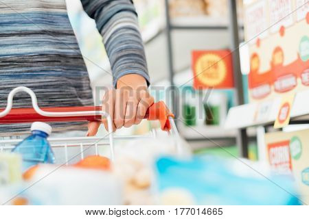 Woman doing grocery shopping at the supermarket and pushing a full shopping cart hand detail close up lifestyle concept